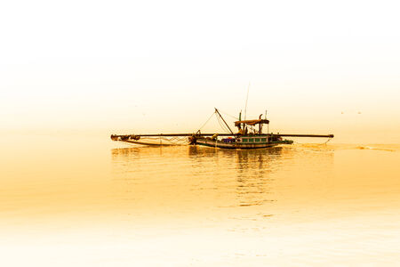 Fishermen collecting shellfish at cockle farming area in the sea photo