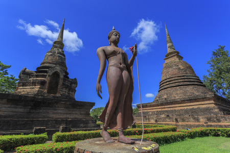 Ancient Buddha statue and pagodas against blue sky at Sukhothai Historical Park, Thailand photo