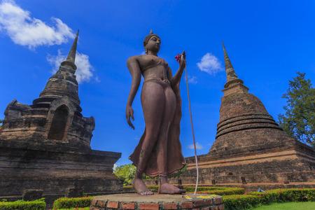 Ancient Buddha statue and pagodas against blue sky at Sukhothai Historical Park, Thailand photo