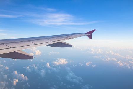 gezichtspunt Wing ramen vliegtuig vliegt boven de wolken in de lucht