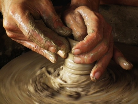 Close-up of potter turning a pot on a potters wheel photo
