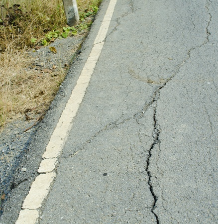 Broken asphalt. Side along the asphalt road collapsed because of erosion.