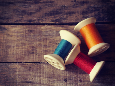thread rolls on wood background old retro vintage style photo