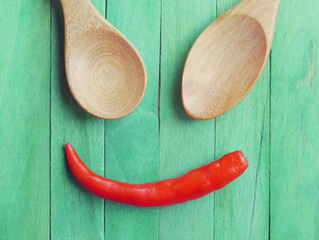 Spoon and Red chili peppers in smile old retro vintage style photo
