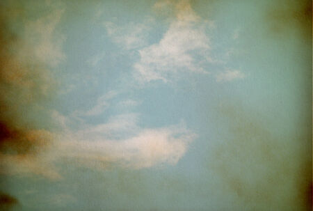 Sky, fog, and clouds on a textured, vintage paper background with grunge stains Stock Photo