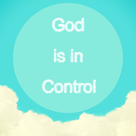 God is in Control  message created from clouds on blue sky with retro filter effect photo