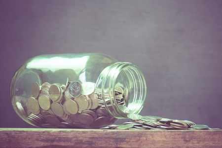 asian coins: Coins spilling out of a glass bottle with filter effect retro vintage style Stock Photo