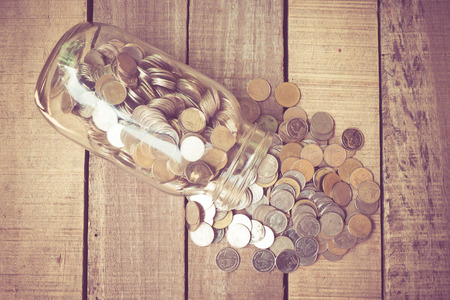 spilling: Coins spilling out of a glass bottle with filter effect retro vintage style Stock Photo