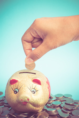 hand putting money coins  with filter effect retro vintage style Stock Photo