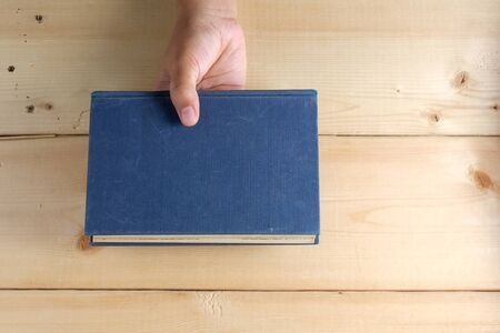two page spread: Hands hold book on wood table