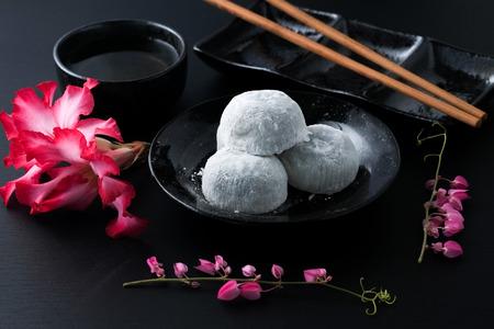 Japanese sweet black sesame daifuku on black wooden background