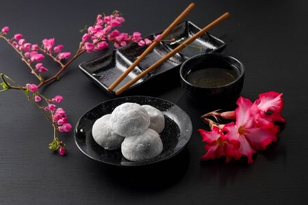 Japanese sweet black sesame daifuku on black wooden background