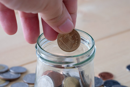 contaduria: business finance. save money for investment concept  coins baht thai and hand Foto de archivo