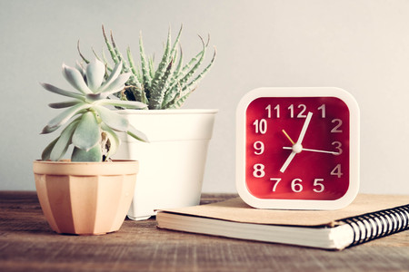 midday: Alarm clock on the wood table with filter effect retro vintage style Stock Photo