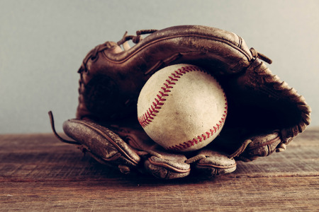 old Baseball and glove on wood background with filter effect retro vintage style