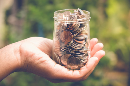 save money for investment concept Hand holding money in jar with filter effect retro vintage style Stock Photo