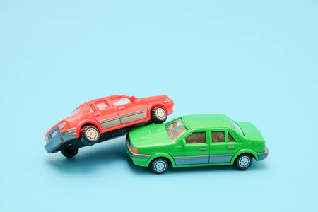 Toy cars in accident on a blue background Stock Photo