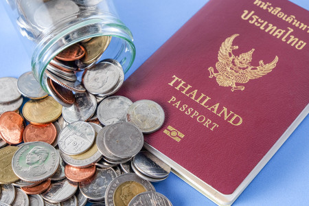 Thailand passport  brown cover and money coin on blue paper background for traveling on holidays