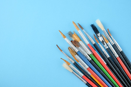 Row of artist paint brushes close up on blue  background