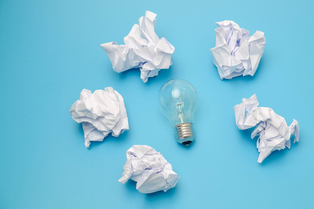 great concept with crumpled office paper and light bulb on a blue background
