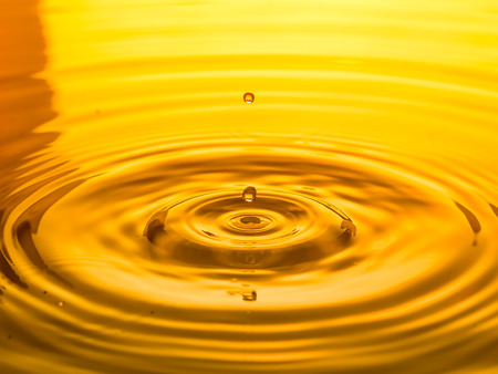 close up of a drop oil on a yellow background Stock Photo