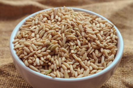 Raw brown rice in a bowl. top view food background Stock Photo