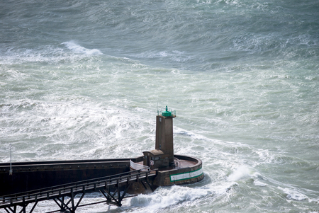 High view waves crashing a lighthouse near coast with background blue aqua sea and dark wood bridge, stormy nature