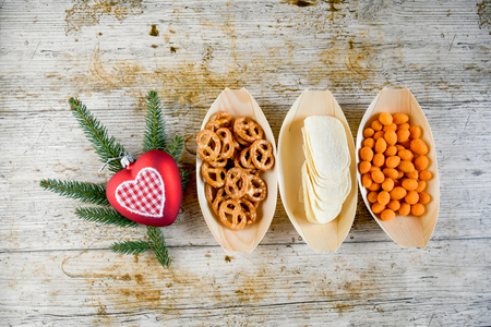 Top view assortiment of snack in bamboo nature bowl in boat shape, on wood board, concept snack for party in christmas holiday with family. Stock Photo