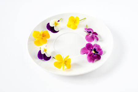 Sweet pansy flowers decorate on empty white circle dish on white background isolated, concept for food style and decoreated special meal in party.
