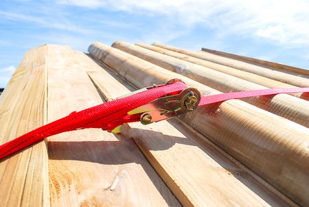 Sangle de remorque ou sangle en nylon rouge et arrimage en métal avec bois et remorque en scierie. Objet aidant à contenir des objets, à stocker et à transporter pour la sécurité et la sécurité. Banque d'images