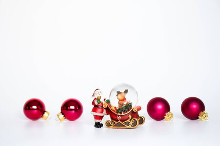 Christmas decoration with red cearmic lamp, red orange candle, red christmas ball and santa clause statue on white background.