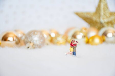 Miniature lover couple with background gold-yellow-gilter christmas ball, merry chistmas and happy new year concept.
