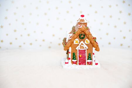 Miniature house bread on white fur with background golden star, ornaments decorate on christmas holiday concept.