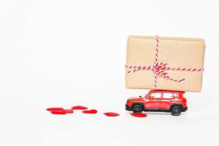 Selecitive focus miniature red car with present heart box on roof with red heart on white background, copy space. Idea surprise gift for special day as valentine's day, anniversary, birthday concept.
