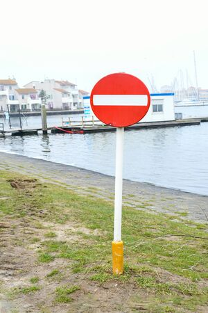 Image no entry sign, a red circle with a white rectangle across its face install  near pier or beach with background sea.  Information and securitry symbol concept. Stock Photo