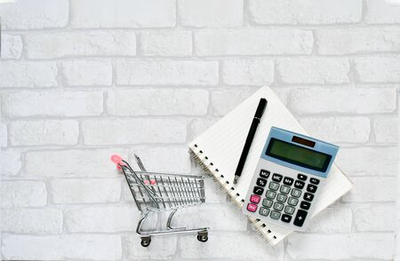 Top view objects , calculator, black pen on  notebook  with small mini shopping cart on  white gray brick background. Idea business and finance concept. sensitive 스톡 콘텐츠