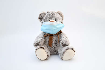 Object, brown gray liitle bear doll wearing a protective medical mask on white background. Infor for  second wave of coronavirus infect ,new normal 's life concept. 写真素材
