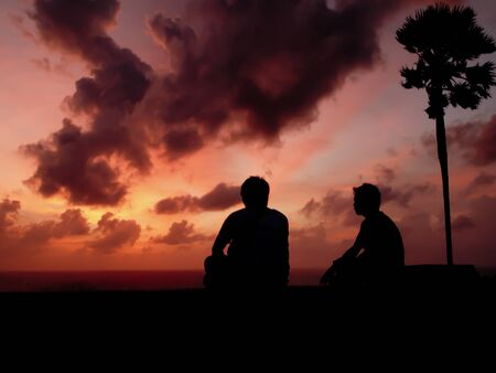 silhouetted two man at sunset photo