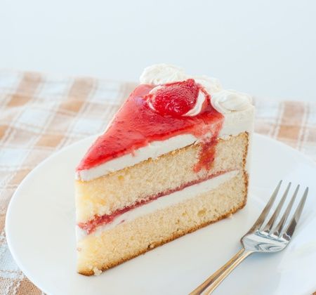 piece of cake with cream and jelly strawberries photo
