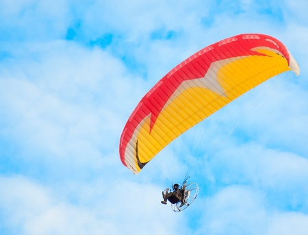 hang glider: man with paraglider flies in the blue sky
