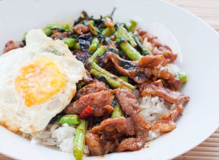 stir fried pork with basil and fried egg on rice, thai traditional food photo
