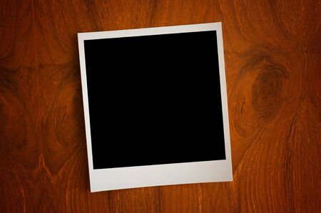 blank photo paper on wooden background photo
