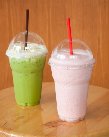 fruit shake: strawberry milkshake and iced green tea on wood table Stock Photo