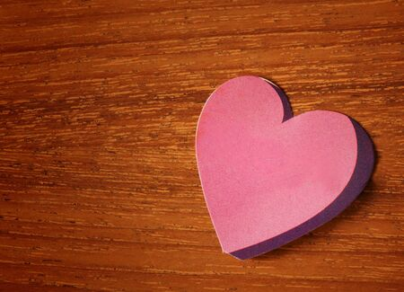 pink heart paper sticker on wood table photo