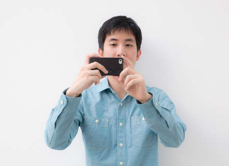 one young man: asian man taking picture with smartphone