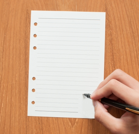 ruled: blank ruled school sheet paper with hand and pen, writing
