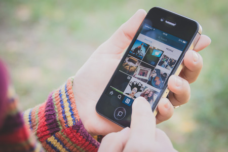 UBON RATCHATHANI, THAILAND - JANUARY 1, 2015: Hand holding Iphone and using Instagram application, Instagram is a popular online social networking service.