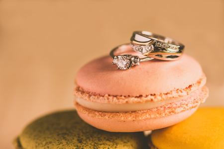 wedding cake: macarons with wedding rings close up shot, retro filter