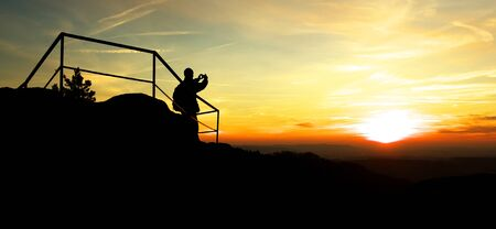 Silhouette of Man on a Vantage Point Taking Photo of Sunset Foto de archivo