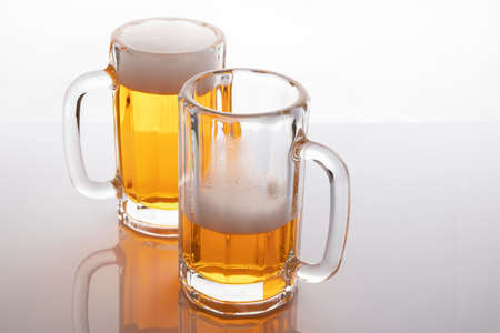 Beer mugs with beer. Beer without frosting. Beer mugs on white backlit background. One glass almost empty and one full. Stock fotó
